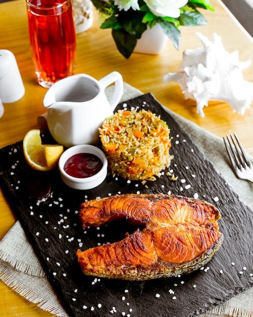 Bistecca di vista laterale da pesce rosso fritto con riso con verdure una fetta di salsa di limone e melograno sul bordo Foto Gratuite