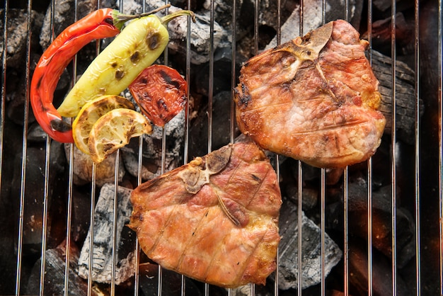 Bistecca e verdura di braciola di maiale su una griglia ardente del bbq Foto Premium