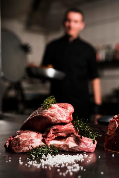 Bistecche di carne cruda con ingredienti sul tavolo Foto Gratuite