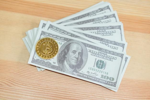 Bitcoin d'oro posto su banconote da 100 dollari Foto Premium