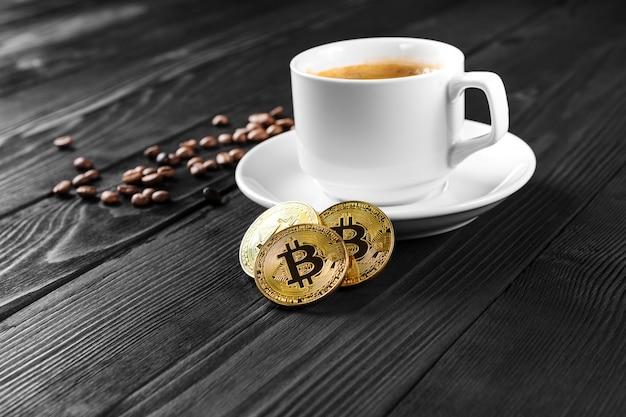 Bitcoin dorato di criptovaluta che sta sulla tazza di caffè isolata Foto Premium