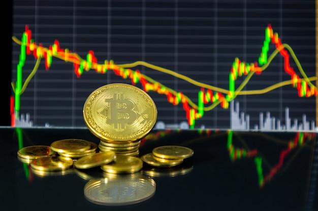 Bitcoin dorato e grafico azionario su tablet. Foto Premium