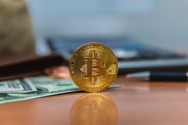 Bitcoin (nuovi soldi virtuali) e banconote da un dollaro. Foto Premium