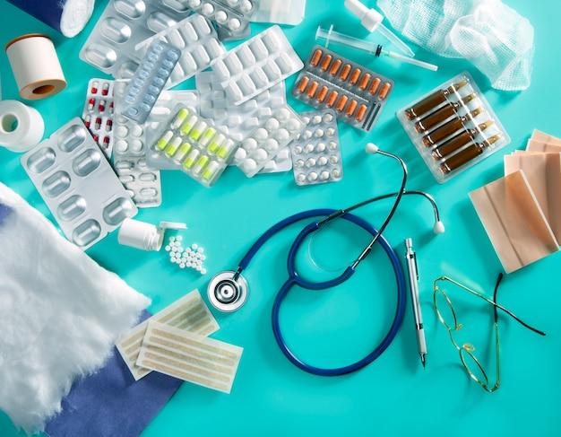 Blister medico pillole scrivania scrivania roba farmaceutica stetoscopio sfondo verde Foto Premium