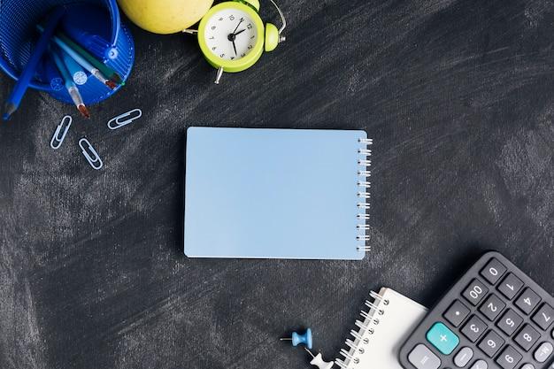 Blocchetto per appunti blu chiuso circondato con cancelleria sulla lavagna Foto Gratuite