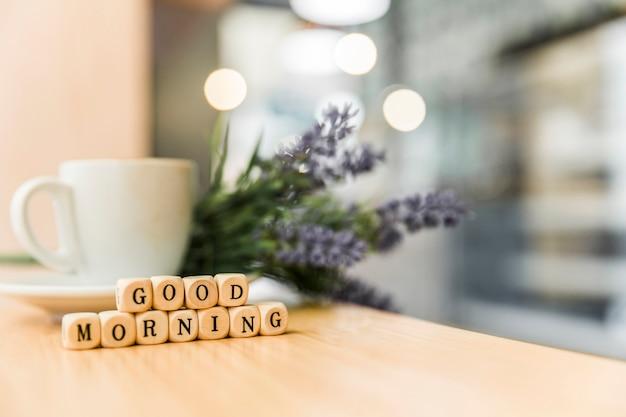 Blocchi cubici di buongiorno con la tazza di caffè sullo scrittorio di legno Foto Gratuite