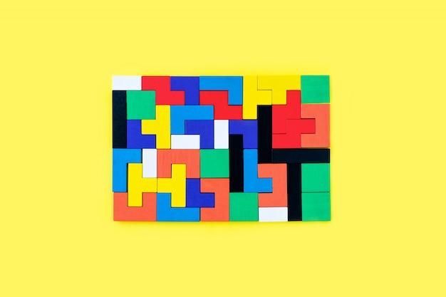 Blocchi di legno colorati di forme diverse puzzle su sfondo giallo. giocattoli naturali ed ecologici. concetto di pensiero creativo e logico. sfondo con blocchi di legno di forme geometriche. Foto Premium