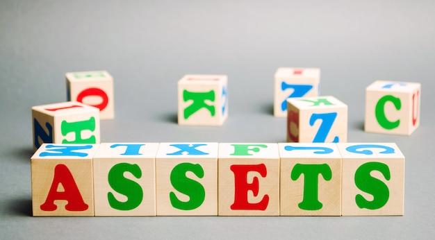 Blocchi di legno con la parola beni e cubi sparsi casualmente. Foto Premium