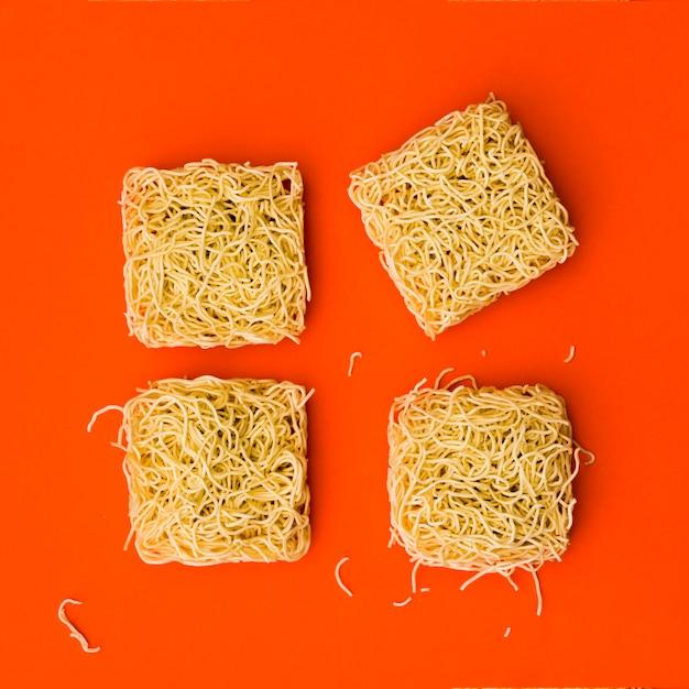 Blocchi di spaghetti istantanei disposti su una superficie arancione brillante Foto Gratuite