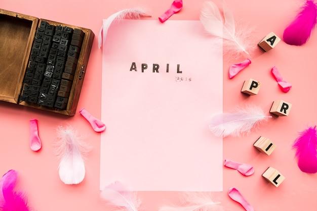 Blocchi tipografici in legno; palloncini; piuma; blocchi di aprile e timbro di aprile su carta bianca su sfondo rosa Foto Gratuite