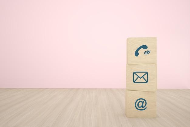 Blocco di cubo di legno tre che impila con l'icona di contatto che sistema in una fila su fondo di legno. concetto di strategia aziendale e piano d'azione. Foto Premium