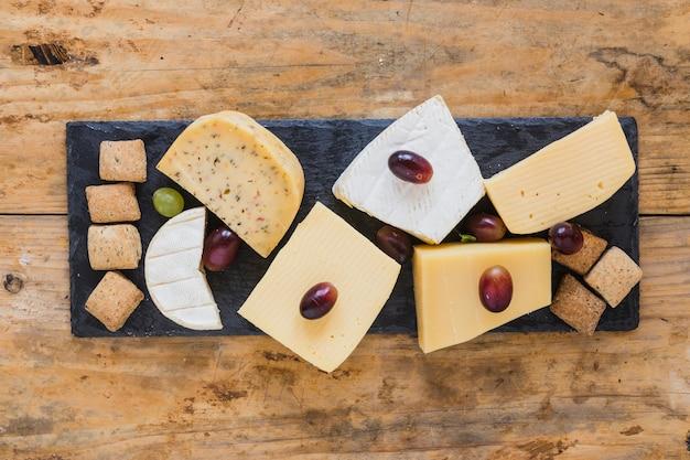 Blocco di formaggio con uva e pasticceria sulla piastra di ardesia sulla scrivania in legno Foto Gratuite
