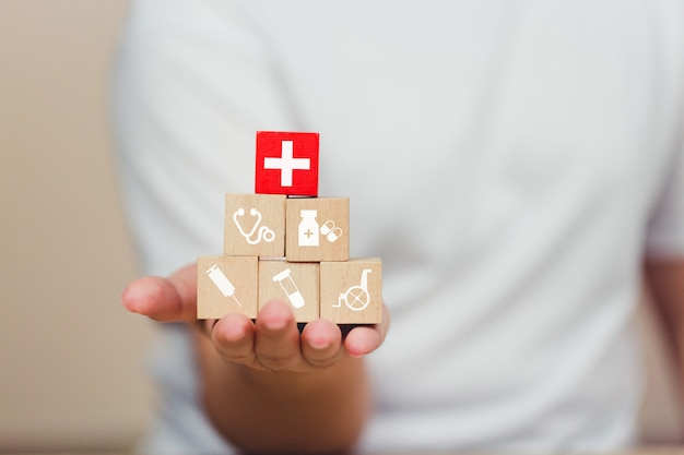 Blocco di legno dell'assicurazione malattia che impila con l'assistenza sanitaria dell'icona medica. Foto Premium