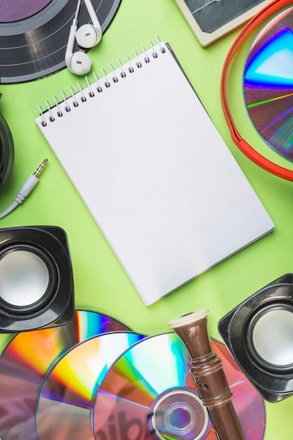 Blocco note a spirale in bianco con altoparlante; compact disc; blocco flauto e auricolare su sfondo verde Foto Gratuite
