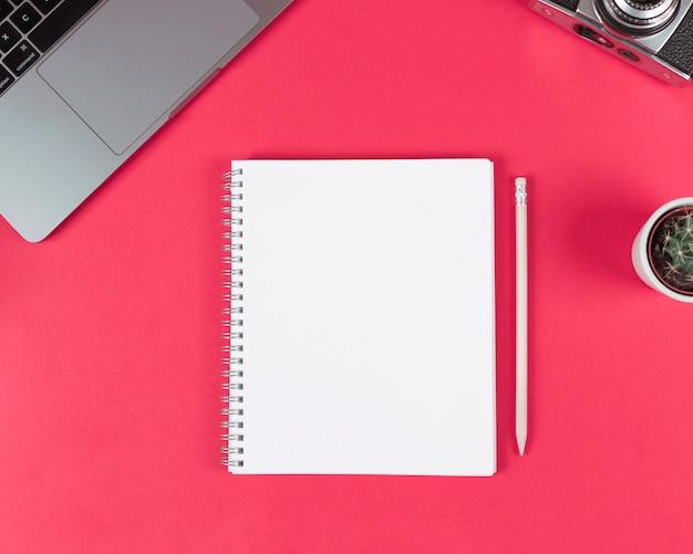 Blocco note a spirale in bianco con matita in legno; il computer portatile; macchina fotografica e cactus pianta su sfondo luminoso Foto Gratuite