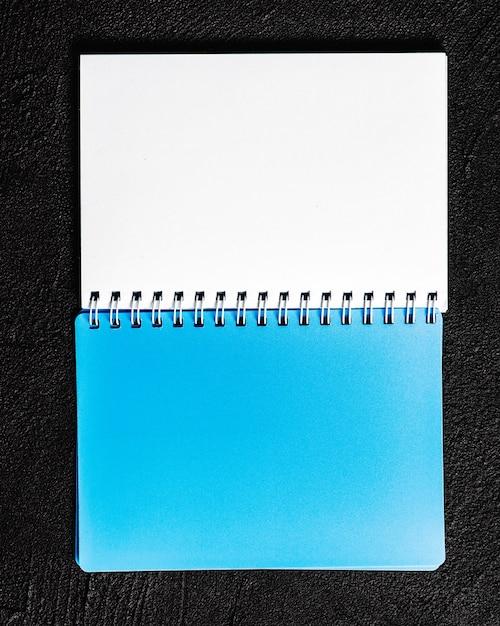 Blocco note che si trova su sfondo nero Foto Premium
