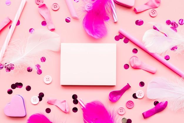 Blocco note vuoto circondato da paillettes; pulsanti; piuma; palloncino; cannuccia su sfondo rosa Foto Gratuite