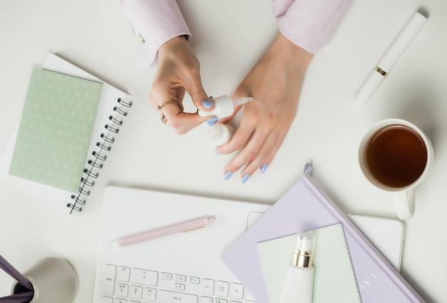 Blogger o consulente di bellezza femminile. lavoro a distanza da casa. freelance laptop, tazza di caffè. cosmetici per lo shopping online. desktop bianco dell'ufficio, disposizione piana, derisione su e copyspace. Foto Premium
