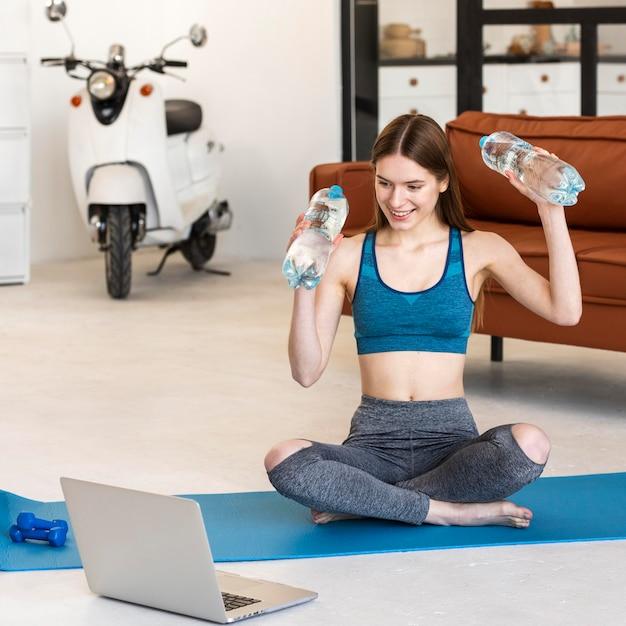 Blogger sportivo che tiene bottiglie d'acqua davanti al computer portatile Foto Gratuite