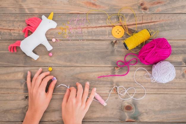 Bobina di filo giallo; lana; filo e perline con unicorno sullo scrittorio di legno Foto Gratuite