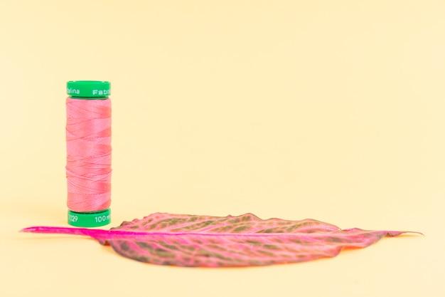 Bobina di filo rosa con una foglia Foto Gratuite