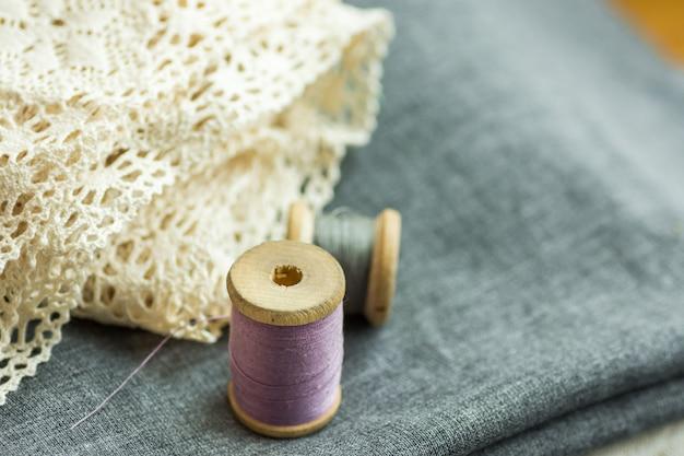 Bobine di legno vintage con fili lilla e grigi su tessuto di lana piegato, pizzo di cotone Foto Premium