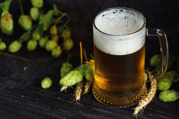 Boccale di birra su sfondo scuro con luppolo verde Foto Premium