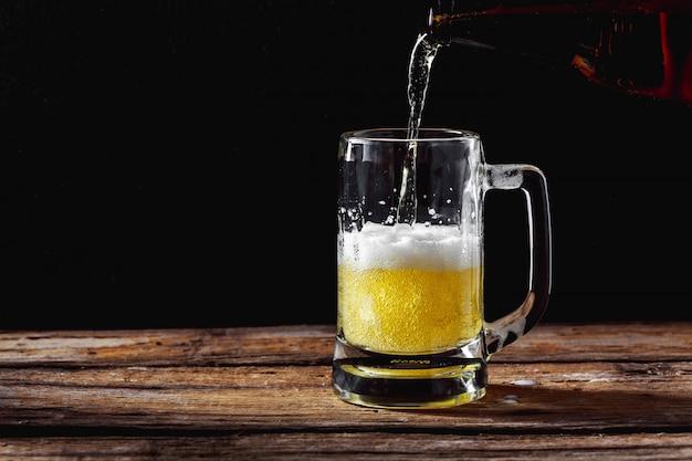 Boccale di birra sul tavolo di legno Foto Premium