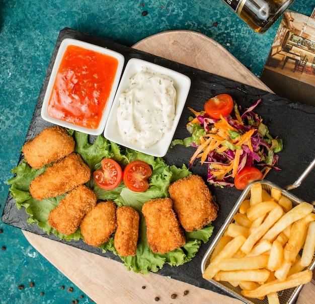 Bocconcini di pollo con patatine fritte, insalata e ketchup Foto Gratuite