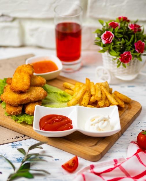 Bocconcini di pollo e patatine fritte, salse di ketchup e maionese su una cucina Foto Gratuite