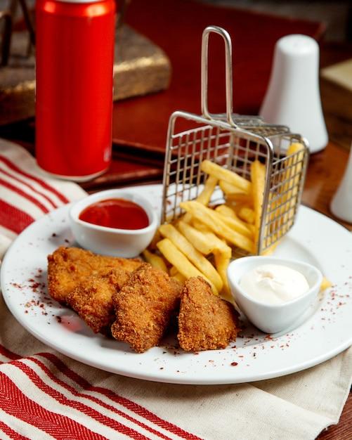 Bocconcini di pollo serviti con maionese e ketchup di patatine fritte Foto Gratuite