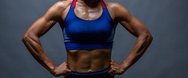 Bodybuilder calvo forte con confezione da sei. culturista donna con addominali perfetti, spalle, bicipiti, tricipiti e petto, istruttore di fitness personale che flette i suoi muscoli. Foto Premium