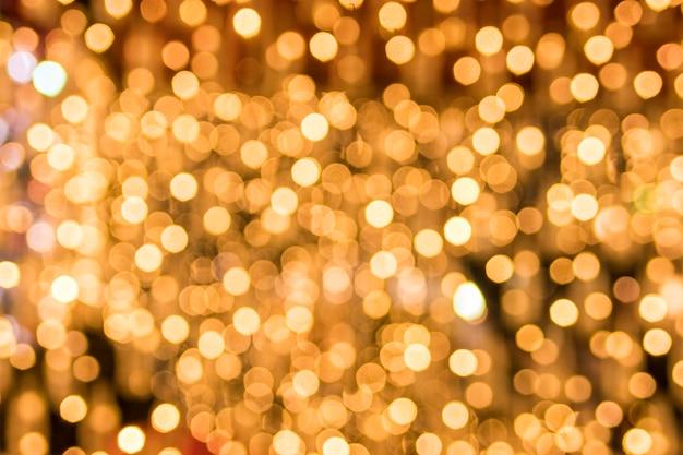 Bokeh astratto della priorità bassa degli indicatori luminosi dorati scintillanti Foto Gratuite