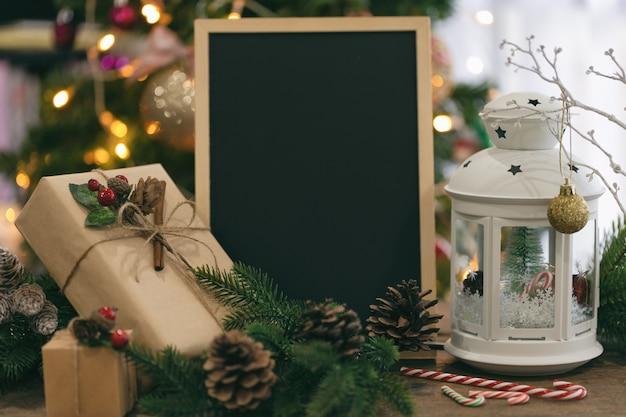 Bokeh di natale decorato con lavagna, confezione regalo, lanterna bianca, pigna, bastoncino di zucchero. Foto Premium