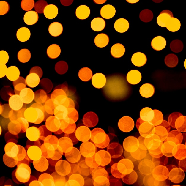 Bokeh giallo astratto unfocused su priorità bassa nera. defocused e offuscato molti luce rotonda Foto Premium