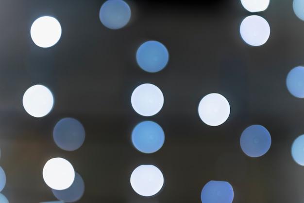 Bokeh incandescente bianco e blu su sfondo scuro Foto Gratuite
