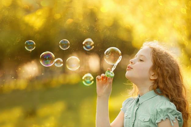 Bolle di sapone di salto della bambina in primavera all'aperto. Foto Premium