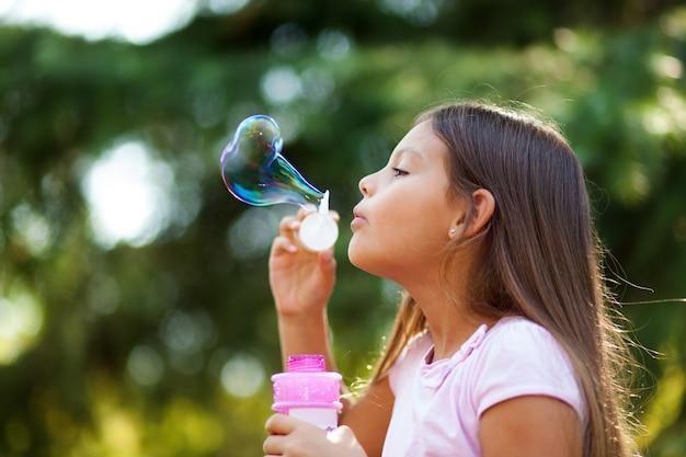 Bolle di sapone di salto della ragazza dei bambini all'aperto Foto Premium