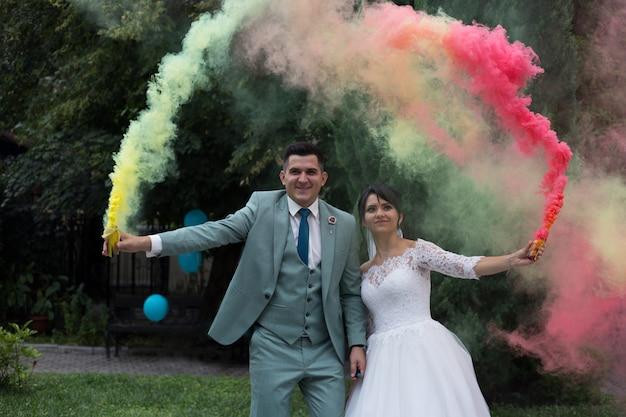 Bombe di fumo di colore chiaro sposi novelli. fumo colorato Foto Premium