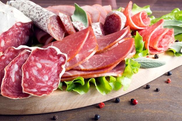Bordo con prosciutto, pancetta, salame e salsicce su fondo di legno. taglio freddo. Foto Premium
