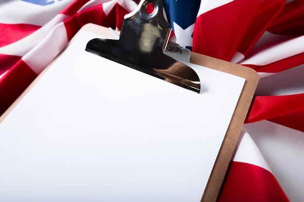 Bordo in bianco della clip e bandiera di usa su fondo di legno Foto Premium
