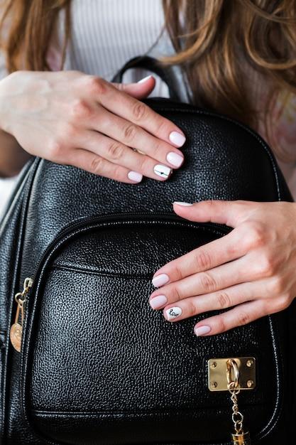 Borsa alla moda della giovane donna alla moda e manicure rosa Foto Premium