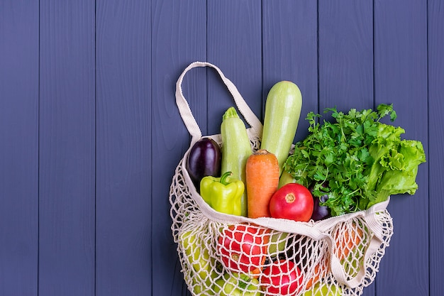 Borsa da negozio ecologica in rete con verdure verdi organiche su legno grigio scuro. Foto Premium