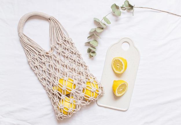 Borsa di macrame shopping a mano con limone su sfondo bianco di cotone Foto Premium