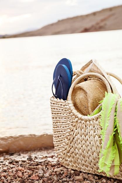 Borsa di paglia estiva e accessori da spiaggia sulla riva Foto Premium