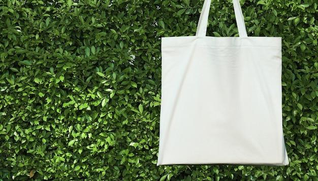 Borsa in bianco di cotone bianco su sfondo verde leavs. concetto eco-compatibile Foto Premium