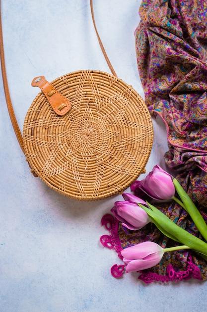 Borsa in rattan alla moda, tulipani e sciarpa su sfondo chiaro. copia spazio, vista dall'alto Foto Premium