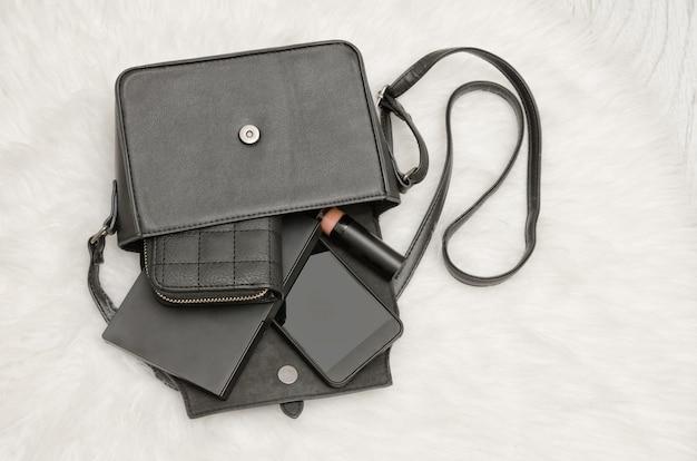 Borsa nera aperta con oggetti caduti, taccuino, cellulare, borsa. la pelliccia bianca su sfondo, vista dall'alto. concetto di moda Foto Premium