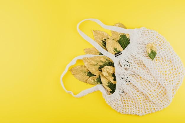 Borsa riutilizzabile della rete commerciale con le foglie verdi e dorate sul fondo giallo di autunno di caduta Foto Premium