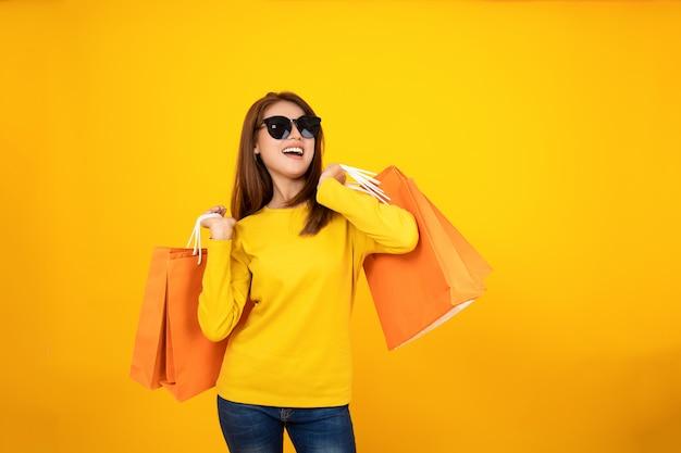 Borse arancio d'acquisto della tenuta graziosa felice asiatica della ragazza che distolgono lo sguardo sul fondo giallo, concetto variopinto di acquisto. Foto Premium